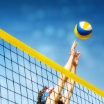 Beachvolley ball player jumps on the net and tries to  blocks the ball